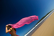 Young Woman Red holding a billowing scarfe in the breeze on an Australian Beach.