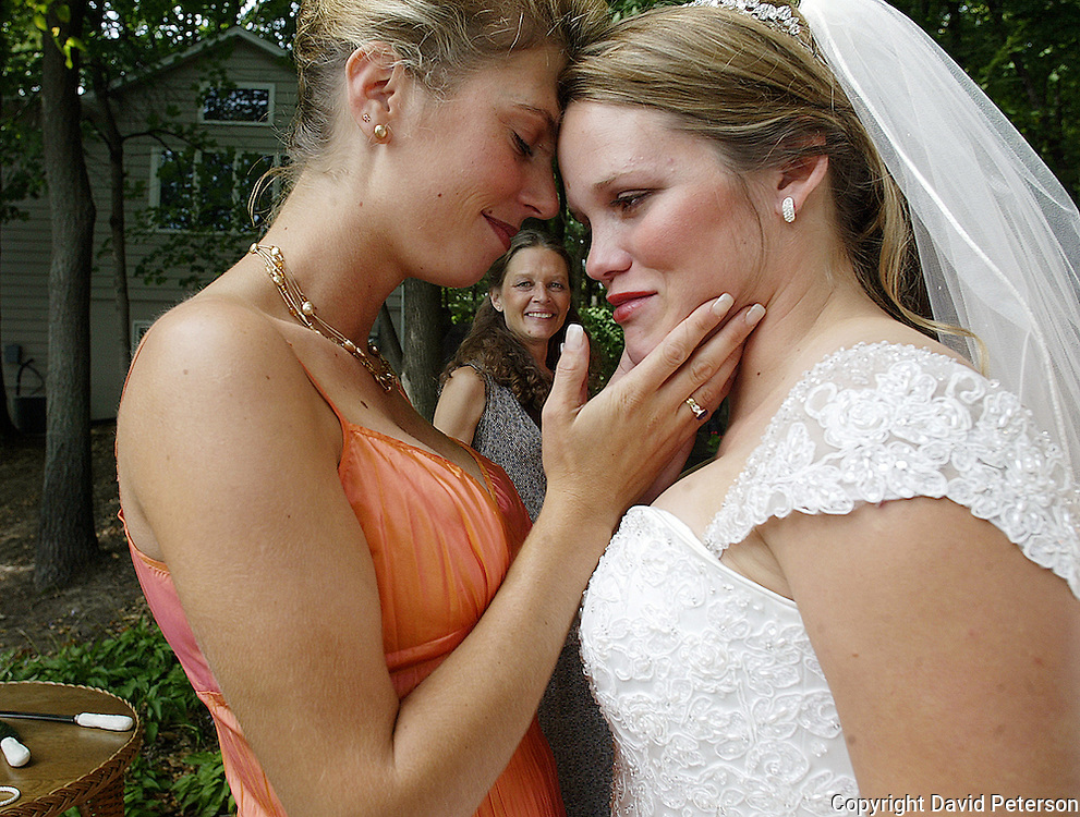 Bride Leaf Sackington, right, shares a tender moment with bridesmaid Jessica Brown before her wedding ceremony in 2004 near Iowa City, Iowa.  Leaf's mother, Flori Schmalfeldt, looks on admiringly.