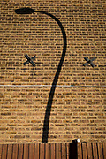 The curved street lights and a twisted shadows on the end wall of a residential house in East Dulwich SE15, in London, England, on 4th December 2019.