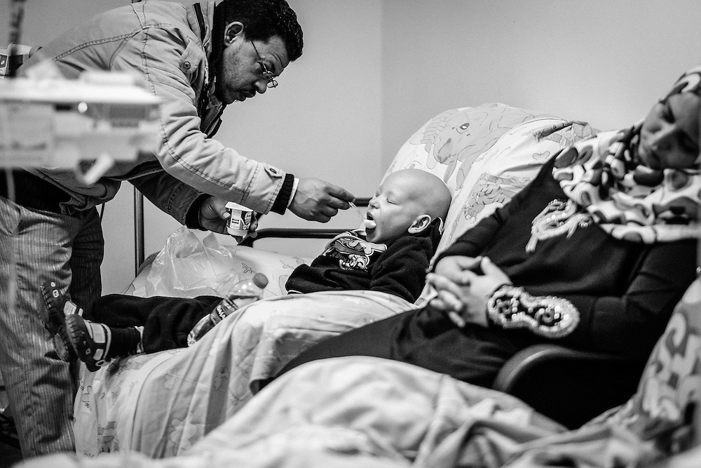 Mostafa, 4, Leukemia, fed by his father during his chemotherapy session.