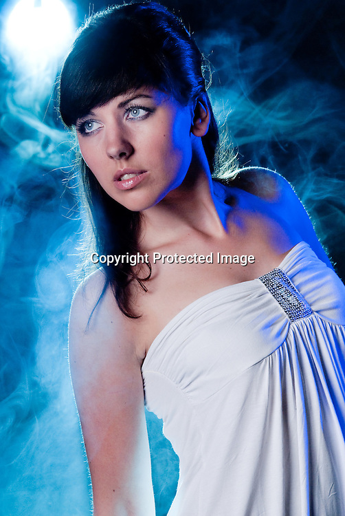 beautiful young lady in smoked background, blue light