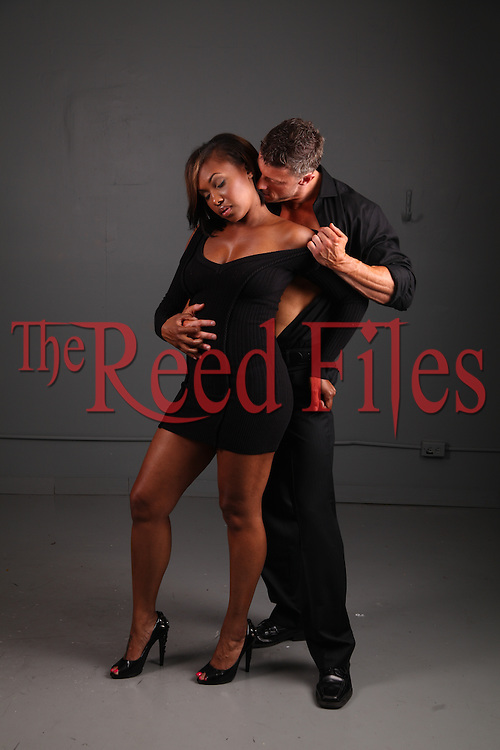 African-American woman in a sexy black dress with a white man