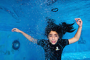 Young girl of 9 holds her breath while floating underwater in a swimming pool