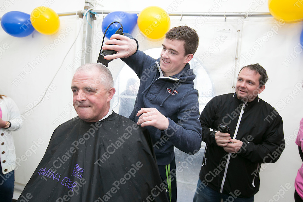 Clare Tony Kelly shaving the Head of Superintendent John Kerin as Clare Manager Davy Fitzgerald looks on  at  the Garda Shave or Dye event in O'Connell Square Ennis. .<br /> Pictured Credit Brian Gavin Press 22