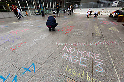 "© Licensed to London News Pictures. 16/11/2014. London, UK. Demonstrators from the ""No More Page 3"" campaign, who are against the use of topless female models in The Sun newspaper, write protest messages in chalk on the pavement to David Dinsmore, The Sun editor, outside the News UK head office at London Bridge in central London on 16th November 2014. Tomorrow, 17th November 2014 marks the 44th anniversary of topless models appearing on Page 3 of The Sun newspaper. Photo credit : Vickie Flores/LNP"