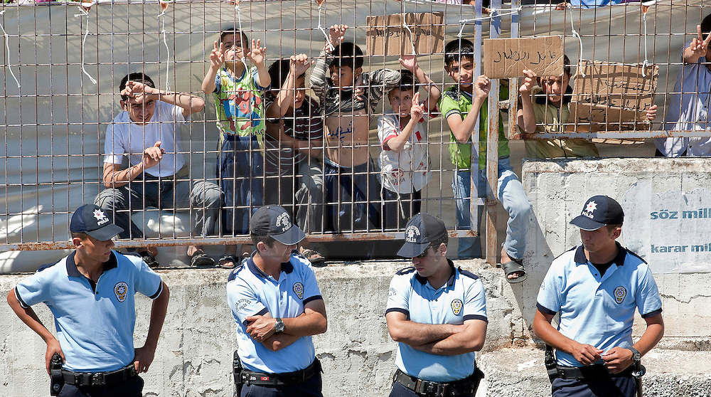© licensed to London News Pictures. HATAY/ TURKEY. PICTURE DATED. 17/06/2011. Turkish police officers protect the Syrian refugees who are demonstrating against President Bashar al-Assad behind the walls of the Turkish Red Crescent camp in the Altinozu district of the Turkish city of Hatay, near the Syrian border, on June 17, 2011. More than 9.000 Syrians have now fled the violence of Syria's 3-month anti-regime uprising against the rule of President Bashar al-Assad and crossed into Turkey in the past ten days. Please see special instructions for usage rates. Photo credit should read TOLGA AKMEN/LNP