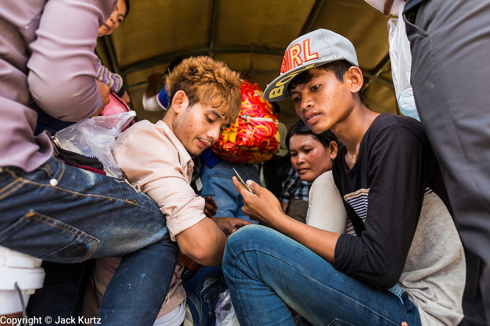 16 JUNE 2014 - POIPET, CAMBODIA: Cambodian migrants sit in a Cambodian army truck waiting to go home after they returned to Cambodia from Thailand. More than 150,000 Cambodian migrant workers and their families have left Thailand since June 12. The exodus started when rumors circulated in the Cambodian migrant community that the Thai junta was going to crack down on undocumented workers. About 40,000 Cambodians were expected to return to Cambodia today. The mass exodus has stressed resources on both sides of the Thai/Cambodian border. The Cambodian town of Poipet has been over run with returning migrants. On the Thai side, in Aranyaprathet, the bus and train station has been flooded with Cambodians taking all of their possessions back to Cambodia.  PHOTO BY JACK KURTZ