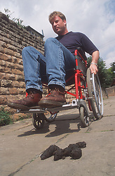 Man with disability; who is manual wheelchair user; approaching pile of dog mess on pavement,