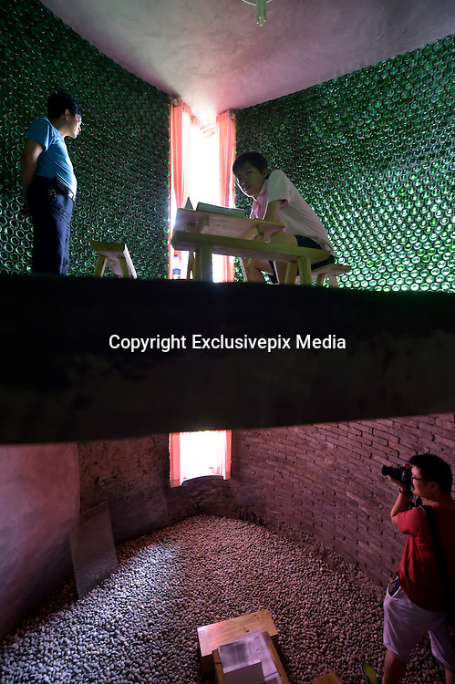 CHONGQING, CHINA - (CHINA OUT) <br /> <br /> Over Eight Thousand Beer bottles To Make A House<br /> <br /> A villager asks Li Rongjun (L), a graduate in Architecture Department from Inner Mongolia University Of Science &amp; Technology, about his self-made 29-squaremeter beer-bottle house at Qijiang District on June 26, 2015 in Chongqing, China. When all graduates planed to hunt for work in market, Li Rongjun from south China\'s Chongqing, dreamed to realize his idea - Architecture works. According to Li Rongjun, beer-bottle house was his model house which could be used as office room with artistry. He dreamed to creat new ideas on architecture and then put them into practice, such as the 29-squaremeter beer-bottle house on second floor which he made with more than eight thousand beer bottles together with father after returning home. The beer-bottle house cost totaly 70,000 RMB (about 11.270 USD), said Li Rongjun\'s father Li Xianshui. <br /> &copy;Exclusivepix Media