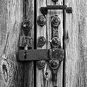 A close up, monochrome shot of an old, rusted lock.