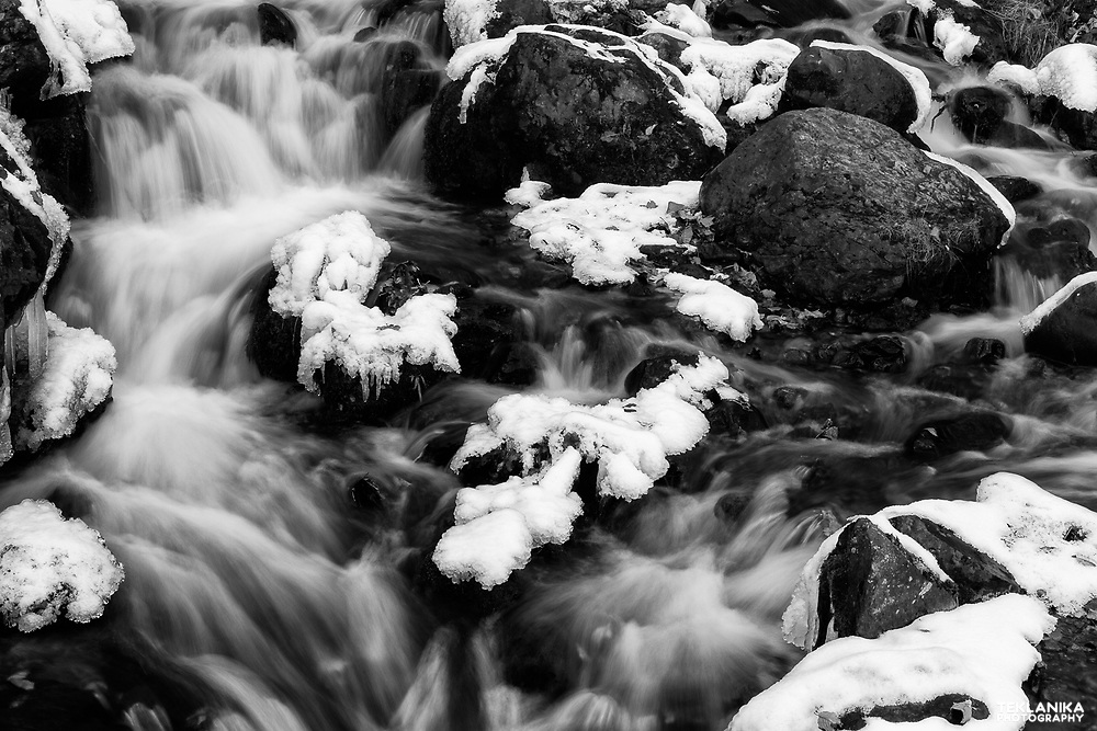 Water flows through an icy Falls Creek.