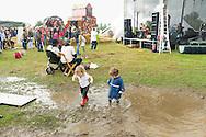 Nederland, Den Bosch, 20140830 <br /> Kinderen stampen met hun laarsjes in de plassen terwijl hun ouders naar muziek luisteren.<br /> Effect Festival - 30 Augustus 2014, De Gemeint 3, bij het Engelermeer tussen Vlijmen en Den Bosch.<br /> eFFect is een manifestatie van lokale duurzame initiatieven die burgers samen van onderop in het leven zetten. Een marktplaats, maar ook workshops door kunstenaars en muziek optredens. Daarnaast ook veel gezonde en alternatieve eettentjes.<br /> <br /> Netherlands, Den Bosch, 20140830.