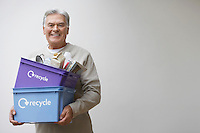 Middle-aged man holding recycling containers smiling