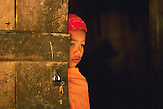 ca. 1985-1995, Yunnan Province, China --- A young novice Theravada Buddhist monk peers from behind a door. --- Image by © Jeremy Horner/Corbis