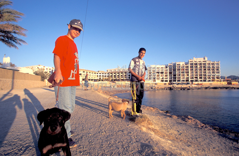 Two youths walk their dogs in Magaluf, Majorca, 2000's.