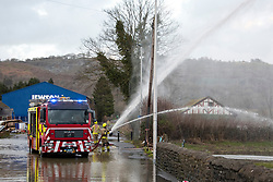© Licensed to London News Pictures. 16/02/2020.  Builth Wells, Powys, Wales, UK. Fire services who have been on call since 01.00hrs this morning, pump water off the A470 road at Builth Wells in Powysafter the river Wye bursts it's banks at Builth Wells in Powys, Wales, UK. due to heavy rainfall yesterday and last night, causing the A483 and A470 road to be closed and traffic diverted. The river level broke the all-time high (4.95 m) at 06.00hrs  this morning at Builth Wells. According to Natural Resources Wales the highest recorded level at Builth Wells was 4.95m on 28/10/98 at 2:45 am (GMT) Photo credit: Graham M. Lawrence/LNP
