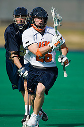 Virginia Midfielder Brian Mcdermott (26) runs past Navy Defenseman Zack Schroeder (51).  The Virginia Cavaliers scrimmaged the Navy Midshipmen in lacrosse at the University Hall Turf Field  in Charlottesville, VA on February 2, 2008.