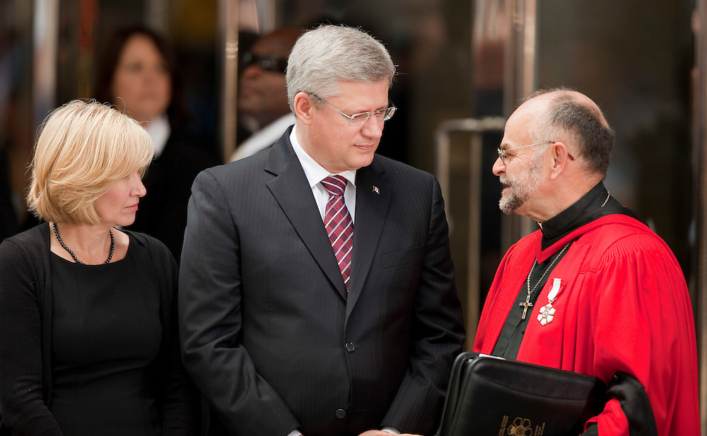 Toronto, Ontario ---11-08-27--- Rev. Brent Hawkes , right, talks with Prime Minister Stephen Harper and his wife Laureen in front of Roy Thompson Hall in Toronto, Ontario before a state funeral for Jack Layton, the late NDP leader August 27, 2011. <br /> AFP/GEOFF ROBINS/STR