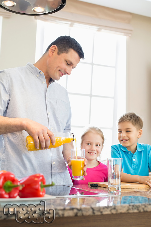 Father serving orange juice for children in kitchen