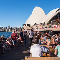 Stylish crowds gather as the sun lowers in the sky at the Opera Bar at the Sydney Opera House in the Circular Quay of Sydney, Australia.
