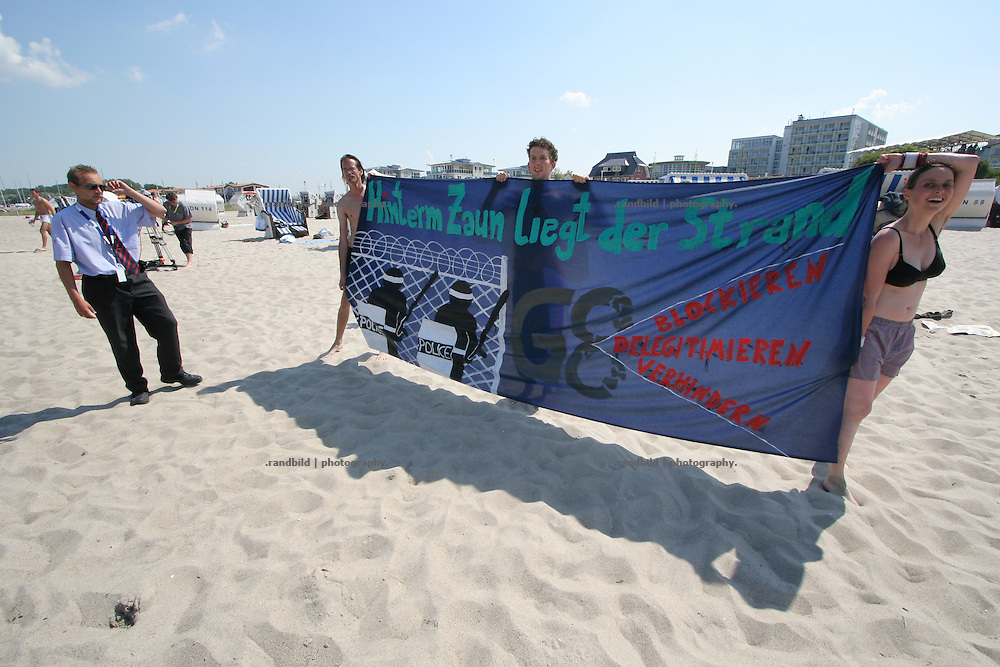 "Am Nachmittag umgingen Anti-G8 Demonstranten den Zaun am Strand des G8-Medienzentrums in Kühlungsborn. Unter dem Motto ""Hinter dem Zaun liegt der Strand"" schlenderten sie entlang des Strandes und badeten in der Ostsee. Polizei udn Sicherheitsdienst brachte die Aktivisten zurück unter den zaun. Mindestens ein Demonstrant wurde in gewahrsam genommen. At the afternoon several anti-G8 aktivists went around the Security fence of the G8 media centre in Kühlungsborn. Unter the motto: ""The beach is behind the fence"" they walked around and took a bath in the Baltic sea."