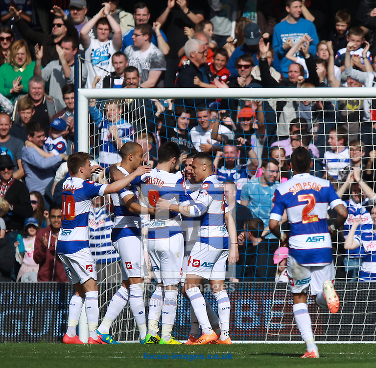 Charlie Austin of Queens Park Rangers is mobbed by team-mates  opening the scoring from the spot against Millwall during the Sky Bet Championship match at the Loftus Road Stadium, London<br /> Picture by John Rainford/Focus Images Ltd +44 7506 538356<br /> 26/04/2014