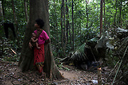 A young Maniq girl and her little sister stand in their camp listening for noises in the forest.<br /> <br /> Evidence suggests that the Maniq, a Negrito tribe of hunters and gatherers, have inhabited the Malay Peninsula for around 25,000 years. Today a population of approximately 350 maniq remain, marooned on a forest covered mountain range in Southern Thailand. Whilst some have left their traditional life forming small villages, the majority still live the way they have for millennia, moving around the forest following food sources. <br /> <br /> Quiet and reclusive they are little known even in Thailand itself but due to rapid deforestation they are finding it harder to survive on the forest alone and are slowly being forced to move to its peripheries closer to Thai communities.