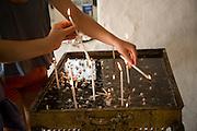 Lighting candles inside Greek orthodox church, Kastrou Monolithos, Rhodes, Greece