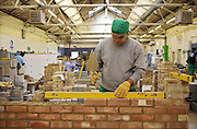 A prisoner on a building course builds a brick wall inside the building workshop at Wandsworth prison. HMP Wandsworth in South West London was built in 1851 and is one of the largest prisons in Western Europe. It has a capacity of 1456 prisoners.