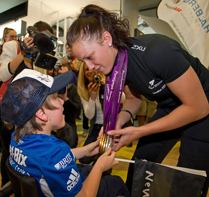Triple gold and silver medallist, swimmer Sophie Pascoe greets Jaden Movold as she arrives at the International Airport from the London 2012 Paralympic Games, Auckland, New Zealand, Wednesday, September 12, 2012.  Credit:SNPA / David Rowland