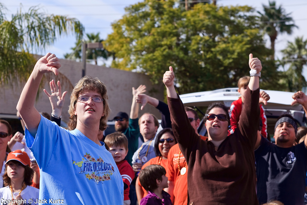 03 JANUARY 2009 -- PHOENIX, AZ: Denise Smith (CQ) LEFT BLUE SHIRT from Glendale, boos Sheriff Joe Arpaio, while Maria Westphal (CQ) RIGHT BROWN SHIRT from Surprise cheers for him during the annual Ft. McDowell Fiesta Bowl parade through Phoenix, AZ. More than 150,000 spectators line the parade routes which starts in north Phoenix and winds down Central Ave and 7th Street before ending in central Phoenix. More than 100 units march in the parade.  PHOTO BY JACK KURTZ
