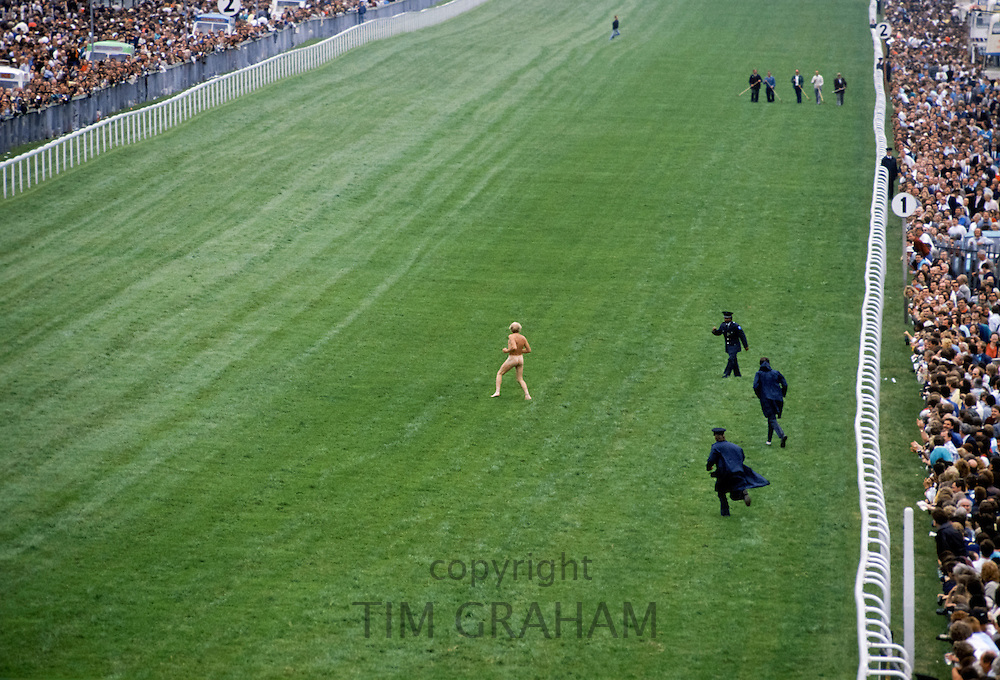 Naked streaker runs across the racetrack chased by police in a breach of security at Epsom Racecourse on Derby Day, UK