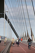In Nijmegen rijden fietsers op het fietspad aan de Oversteek, de nieuwe verbinding over de Waal aan de noordkant van Nijmegen.<br /> <br /> In Nijmegen cyclists are riding at the bike line at The Crossing, the new connection crossing the Waal at the north side of Nijmegen.