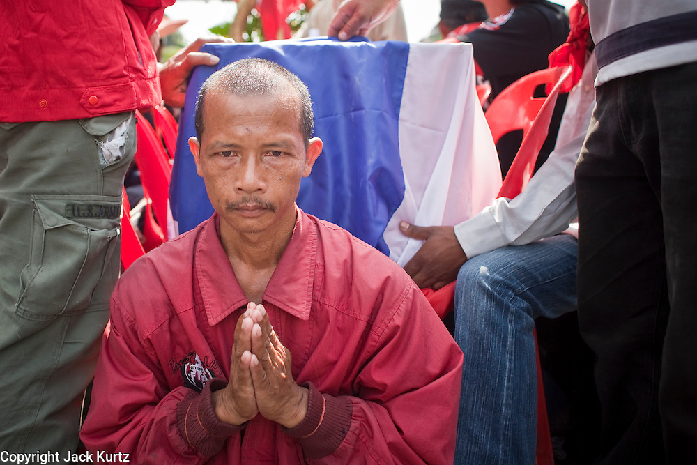 Apr. 12, 2010 - BANGKOK, THAILAND: A Red Shirt guard prays as he escorts the coffin of a man killed Saturday through the streets of Bangkok Monday. The funeral cortege for the Red Shirts killed in the violent crackdown Saturday wound through Bangkok Monday. Thousands of mourners came out to pay respects for dead Red Shirts. 21 people, including 16 Thai civilians were killed when soldiers tried to clear the Red Shirts' encampment in Bangkok. Thousands more came out to call for the government of Thai Prime Minister Abhisit Vejjajiva to step down. Today Gen. Anupong Paojinda, the Chief of Staff of the Thai Army, reiterated that the Army would not use violence to break up the protests and joined the call for the Prime Minister to call new elections. This is the beginning of Songkran, Thai New Year's week, and the government has cancelled the official festivities fearing more violence. It was during last year's Songkan festivities that the Thai Army and police used force to break up the Red Shirt protests. That protest is now called the Songkran Riots.     Photo By Jack Kurtz