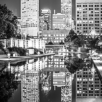Indianapolis skyline at night black and white photo with the reflection of downtown city buildings on the Indiana Central Canal. The canal was built in the 1800s and serves as a recreational attraction along Canal Walk.