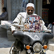 A Yemeni man smiles as he drives his motorcyle emblazoned with pictures of Sadaam Hussein in the town of Seiyun. Sadaam Hussein pictures are quite common in Yemen, gracing kiosks, cars, and shops.