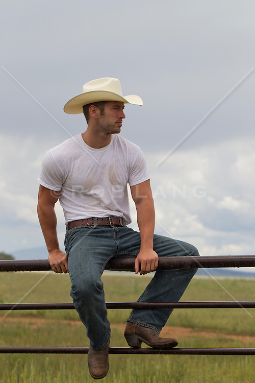 Cowboy sitting on a fence looking out on the ranch