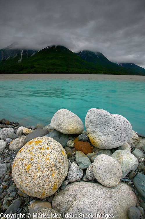 Aqua water of Melt creek mixes with the brown silty water of the Tatshenshini River in the Noisy Range of BC. Canada.