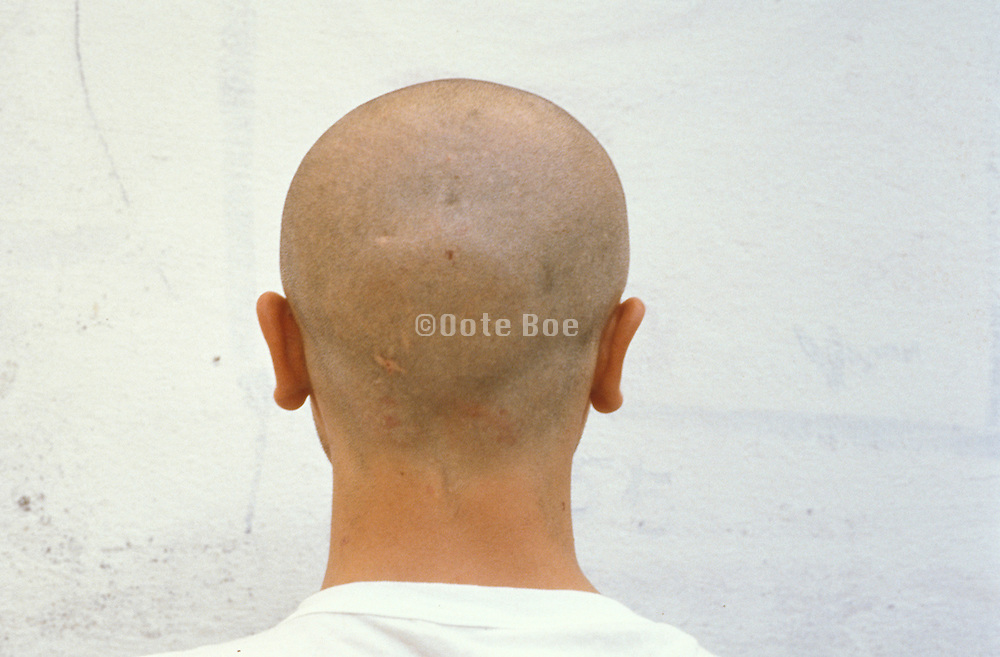 a bald man facing a concrete wall