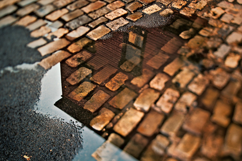 Front of Bridge Cafe reflected in puddle in street, New York, NY, US