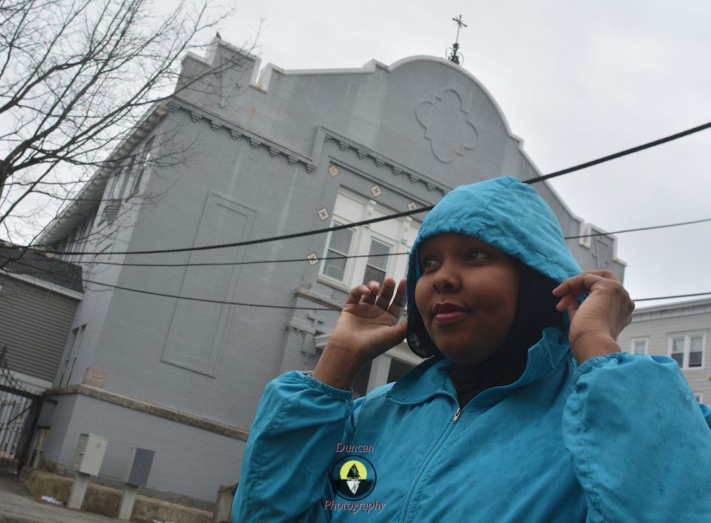 LEWISTON, Maine,  -- 4/2/16 --  Fahmo Ahmed, 28, adjusts her coat to protect her hijab from the rain as she walks from her home to a community housing meeting nearby. She came to the United States from Somalia 12 years ago, graduated from Edward Little, earned her citizenship and working her way towards graduation from college this year. A vibrant community organizer and advocate for women's reproductive rights, she hopes someday to run for office. Photo by Roger S. Duncan for The Forecaster