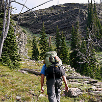 A backpackers climbs off-trail to a high ridge deep in the backcountry of Montana's Rattlesnake Wilderness.