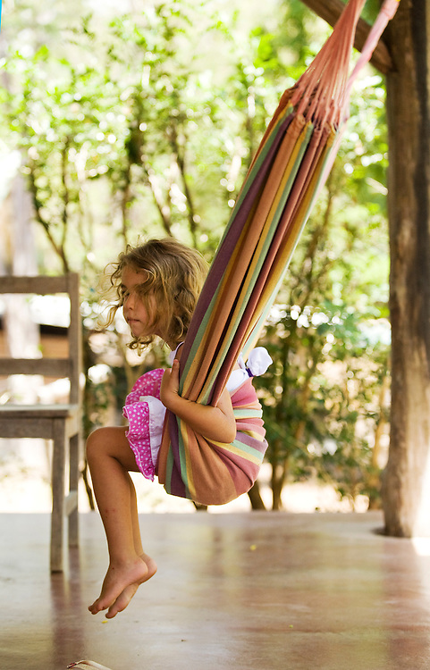 A young girl perches on a hammock on the porch of a Costa Rican house