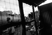 NAIROBI, KENYA - AUGUST 20, 2011: Pedestrians and shop owners watch a train go by in Kibera slum.