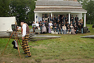 A photographer wearing period dress adjusts his camera before taking a picture of members of the 124th New York State Volunteers during a Civil War reenactment at the Orange County Farmers Museum on Sept. 23, 2006.