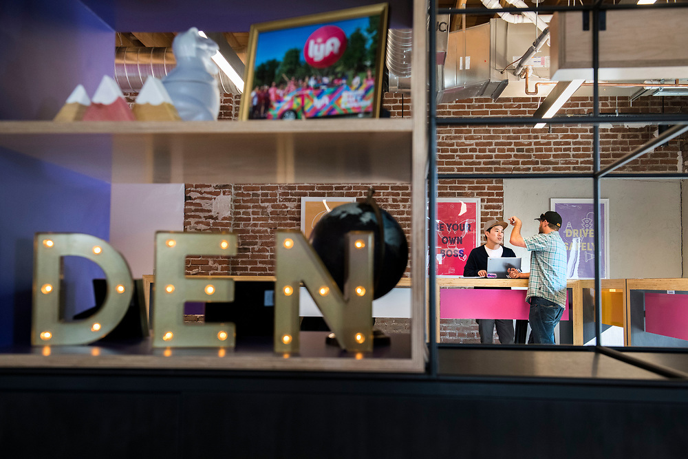 DENVER – NOV. 3. Lyft driver Soren McCarthy, 48, of Wash Park, gestures as he chats with Lyft community associate Nhan Le, 38, center, of Englewood, during an appointment at Lyft's newly opened office in Steam on the Platte in Denver's Sun Valley neighborhood. Steam on the Platte is a new and historic reuse space recently developed at 14th and Zuni streets. (Photo by Andy Colwell/Special to The Denver Post)