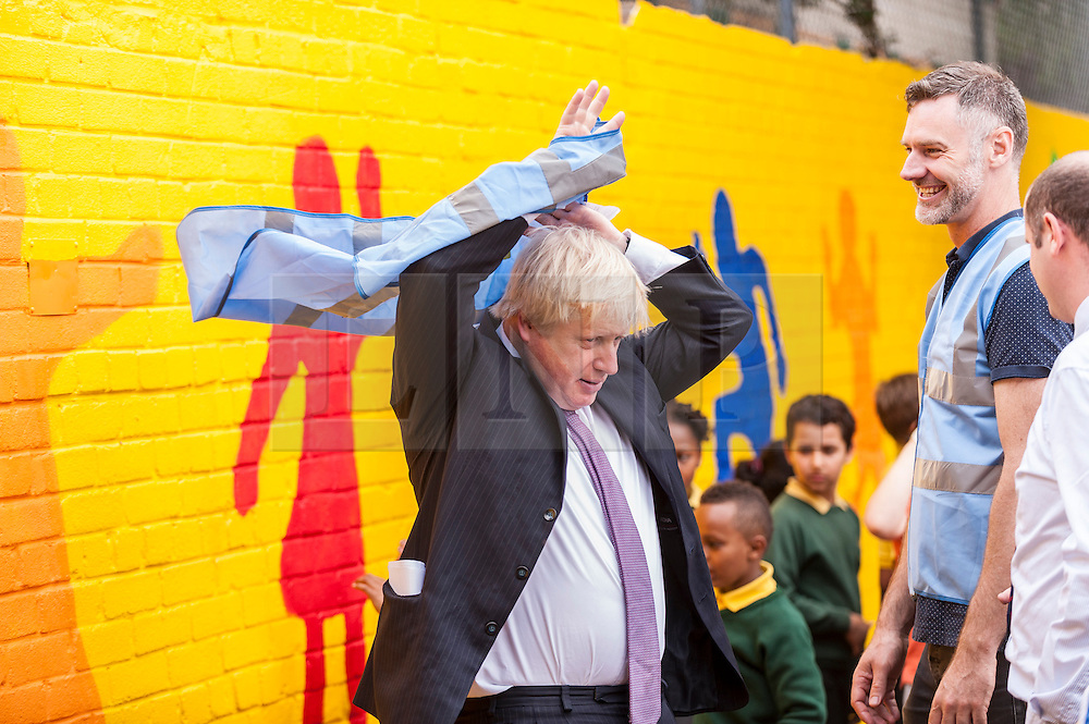 © Licensed to London News Pictures. 16/07/2015. London, UK. The Mayor of London, Boris Johnson, visits Marcus Garvey Park near Hammersmith to join local volunteers clearing the park, assisting local schoolchildren to paint a colourful wall mural and to officially launch the start of this summer's biggest ever Capital Clean-up.  The initiative, funded by the Mayor of London, aims to improve previously neglected areas of the city with the help of nearly 3,000 volunteers. Photo credit : Stephen Chung/LNP