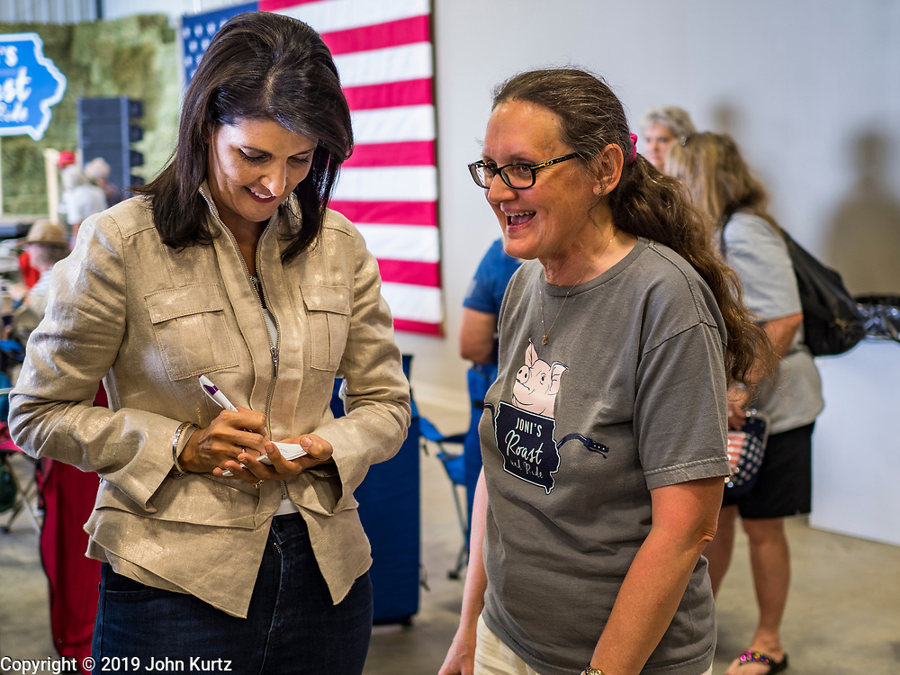"""15 JUNE 2019 - BOONE, IOWA: Former UN Ambassador NIKKI HALEY signs an autograph at """"Joni's Roast and Ride,"""" an annual fund raiser held by US Senator Joni Ernst (R-IA). Ernst, Iowa's junior US Senator, kicked off her re-election campaign during the """"Roast and Ride"""", an annual fund raiser and campaign event has she held since originally being elected to the US Senate in 2014. PHOTO BY JACK KURTZ"""
