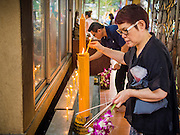"""14 FEBRUARY 2014 - BANGKOK, THAILAND: A woman lights candles to make merit on Makha Bucha Day at Wat That Thong. The aims of Makha Bucha Day are: not to commit any kind of sins, do only good and purify one's mind. It is a public holiday in Cambodia, Laos, Myanmar and Thailand. Many people go to the temple to perform merit-making activities on Makha Bucha Day. The day marks four important events in Buddhism, which happened nine months after the Enlightenment of the Buddha in northern India; 1,250 disciples came to see the Buddha that evening without being summoned, all of them were Arhantas, Enlightened Ones, and all were ordained by the Buddha himself. The Buddha gave those Arhantas the principles of Buddhism, called """"The ovadhapatimokha"""". Those principles are:  1) To cease from all evil, 2) To do what is good, 3) To cleanse one's mind. The Buddha delivered an important sermon on that day which laid down the principles of the Buddhist teachings. In Thailand, this teaching has been dubbed the """"Heart of Buddhism.""""   PHOTO BY JACK KURTZ"""