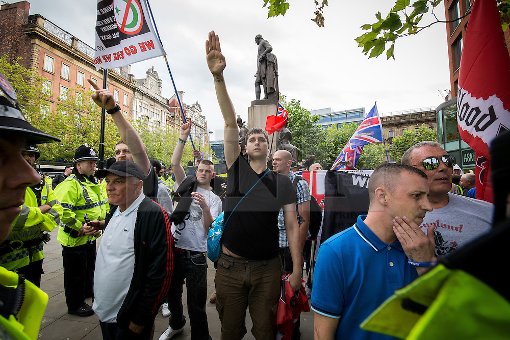 """© Licensed to London News Pictures . 22/08/2015 . Manchester , UK . A far-right supporter (c) gives a Nazi salute . Far-right nationalist group , """" North West Infidels """" and Islamophobic , anti-Semitic and white supremacist supporters , hold a rally in Manchester City Centre . Photo credit : Joel Goodman/LNP"""